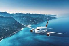 L'avion vole au-dessus des îles et de la mer au lever de soleil en été Photo stock