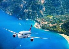 L'avion vole au-dessus des îles et de la mer au lever de soleil en été Images stock