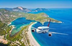 L'avion vole au-dessus des îles et de la mer au lever de soleil en été Image stock