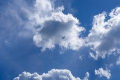 L'avion vole contre le ciel bleu avec des nuages photos libres de droits