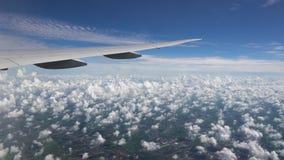 L'avion vole dans le ciel bleu Nuages et ville blancs ci-dessous sous l'aile des avions banque de vidéos