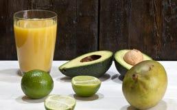 L'avocado ? dimezzato, mango, calce su una tavola di legno immagini stock