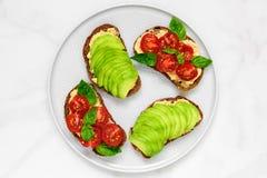 L'avocado ed i pomodori tosta con il hummus ed il basilico in un piatto sopra fondo di marmo bianco Alimento del vegano Immagini Stock Libere da Diritti