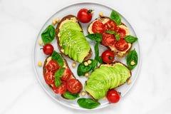 L'avocado ed i pomodori tosta con il hummus, il sesamo ed il basilico in un piatto sopra fondo di marmo bianco Alimento del vegan Fotografie Stock