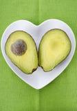L'avocado ha tagliato a metà sul piatto di forma del cuore Immagini Stock