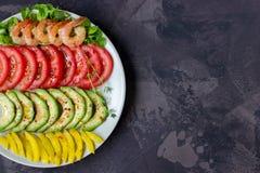 L'avocado, il pomodoro, il pepe ed i gamberetti su un piatto hanno allineato con le file Fotografia Stock