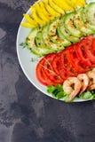 L'avocado, il pomodoro, il pepe ed i gamberetti su un piatto hanno allineato con le file Fotografie Stock