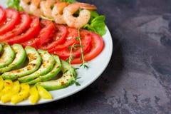 L'avocado, il pomodoro, il pepe ed i gamberetti su un piatto hanno allineato con le file Immagini Stock