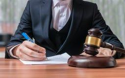 L'avocat écrit et marteau dans l'avant Justice et concept de loi image libre de droits