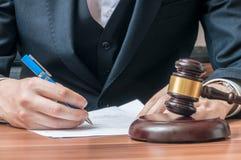 L'avocat écrit sur le document Marteau en bois dans l'avant photo libre de droits