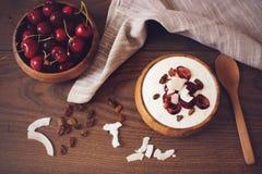 L'avoine s'écaille avec du yaourt et des fruits Cerises, raisins secs et pommes chips de noix de coco Concept sain de nourriture  images stock