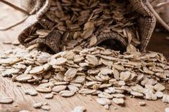L'avoine s'écaille céréale dans le sac à toile de jute sur la table en bois Image libre de droits