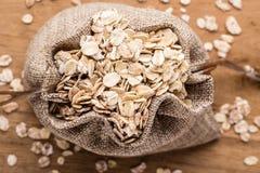 L'avoine s'écaille céréale dans le sac à toile de jute sur la table en bois Photo libre de droits