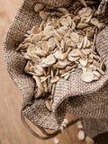 L'avoine s'écaille céréale dans le sac à toile de jute sur la table en bois Photos stock
