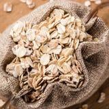 L'avoine s'écaille céréale dans le sac à toile de jute sur la table en bois Images stock