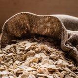 L'avoine s'écaille céréale dans le sac à toile de jute sur la table en bois Photographie stock