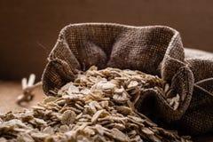 L'avoine s'écaille céréale dans le sac à toile de jute sur la table en bois Images libres de droits
