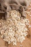 L'avoine s'écaille céréale dans le sac à toile de jute sur la table en bois Photo stock