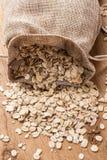 L'avoine s'écaille céréale dans le sac à toile de jute sur la table en bois Image stock