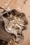 L'avoine s'écaille céréale dans le sac à toile de jute sur la table en bois Photographie stock libre de droits