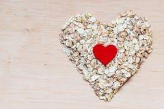 L'avoine s'écaille céréale en forme de coeur sur la surface en bois Photo stock