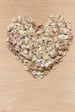 L'avoine s'écaille céréale en forme de coeur sur la surface en bois Photographie stock libre de droits