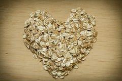 L'avoine s'écaille céréale en forme de coeur sur la surface en bois Photographie stock
