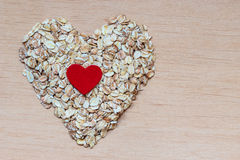 L'avoine s'écaille céréale en forme de coeur sur la surface en bois Photos libres de droits
