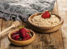 L'avoine s'écaille dans la cuvette avec la fraise sur la table en bois photo libre de droits
