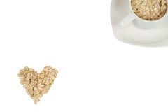 L'avoine s'écaille dans une forme de coeur et de tasse blanche avec la soucoupe Photos stock