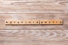 L'avventura attende la parola scritta sul blocco di legno L'avventura attende il testo sulla tavola di legno per vostro desing, c immagine stock