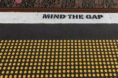 L'avvertimento di lacuna di mente ad una stazione ferroviaria, con i perni gialli per i ciechi immagine stock libera da diritti