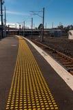 L'avvertimento di lacuna di mente su un binario ad una stazione ferroviaria, con i perni gialli per i ciechi fotografie stock libere da diritti