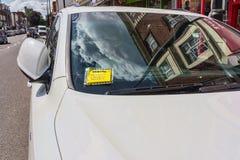 L'avviso della tassa di pena (che parcheggia benissimo) allegato al tergicristallo dell'automobile bianca ha parcheggiato in via  Immagine Stock