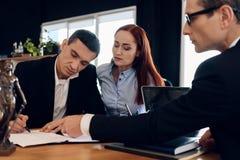L'avvocato di divorzio mostra ad uomo dove firmare l'accordo della dissoluzione del matrimonio immagine stock