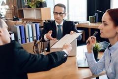 L'avvocato serio dà l'uomo adulto al documento del segno sul divorzio Coppie che passano attraverso le carte di firma di divorzio immagine stock libera da diritti