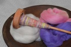L'axe en bois avec la main a tourné le fil dans une cuvette en bois de vagabondage de laine photo stock