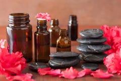 L'azalée d'huile essentielle fleurit les pierres noires de massage Image libre de droits