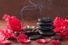 L'azalea fiorisce i bastoni neri di incenso delle pietre di massaggio per aromather Fotografia Stock