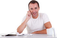 L'centrale-età sorridente equipaggia la seduta allo scrittorio sul telefono fotografie stock