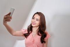 L?cheln asiatisch, ein selfie mit Smartphone auf wei?em Hintergrund nehmend stockbilder