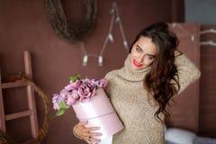 L?chelnde Frau in der Pyjamaholdinggeschenkbox und Betrachten der Kamera, Valentinsgru?tageskonzept lizenzfreies stockbild