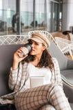 L?chelnde Frau im Flughafencaf? mit Tasse Kaffee stockfotografie