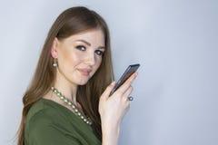 L?chelnde Frau zeigt auf stehende begrenzte Sch?rfentiefe des Smartphone lizenzfreie stockfotografie