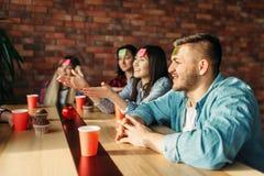 L?chelnde Freunde, die Aufkleberanmerkungen zur Stirn spielen stockfotografie