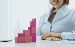 L?chelnde Gesch?ftsfrau, die ein erfolgreiches Finanzdiagramm errichtet stockfotografie
