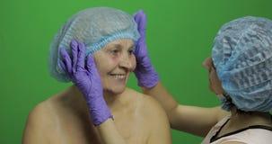 L?chelnde ?ltere Frau im sch?tzenden Hut Plastischer Chirurg, der Frauengesicht ?berpr?ft stock video