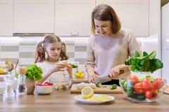 L?chelnde Mutter und Tochter 8, 9 Jahre altes zusammen kochen im K?chengem?sesalat Gesunde Hauptnahrung, Kommunikationselternteil lizenzfreie stockfotos
