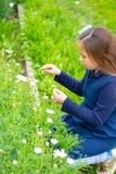 L?chelndes kleines Latina-M?dchen im Garten, der Blumen ausw?hlt stockfotos