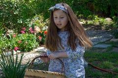 L?chelndes kleines Latina-M?dchen im Kleid des Gartens im Fr?hjahr mit Korb lizenzfreie stockfotografie